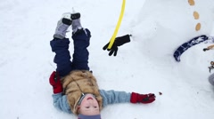 Little boy lies near upside down snowman at winter day Stock Footage