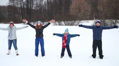 Happy family of four fall into snow and depict angels at winter day Stock Footage
