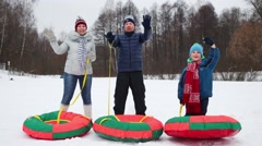 Mother, father and son with snow tubes wave hands in winter day Stock Footage