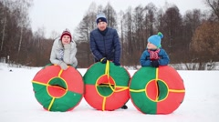Mother, father and son pose with snow tubes in winter day Stock Footage