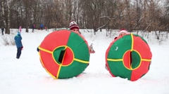 Two women throw up snow tubes outdoor at winter day Stock Footage