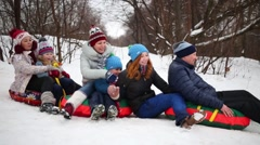 Six happy people on snow tubes down hill at winter day Stock Footage