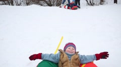 Two women let go down from hill two boys on snowtubes Stock Footage