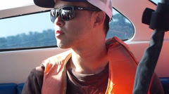 Asian young man wearing life jacket on the boat. Abstract security and safety Stock Footage
