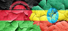 Malawi flag with Ethiopia flag on a grunge cracked wall Stock Illustration