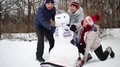 Three adults pushing down snowman from hill at winter Stock Footage