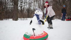 Woman drags snowman with scarf on snowtube at winter day Stock Footage