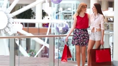 Two girls with purchases stand near railing and go away in mall Stock Footage