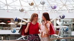 Two women with purchases talk and smile in modern mall Stock Footage
