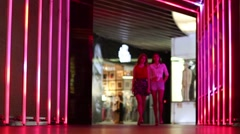 Two pretty women go near illuminated wall in shopping center Stock Footage