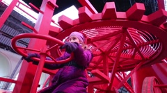 Girl on red mechanism in exhibition Mechanics of Marvel Stock Footage