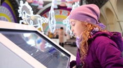 Girl in hat reads text from big touch screen in hall Stock Footage