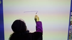Back of girl painting on big interactive touch screen Stock Footage