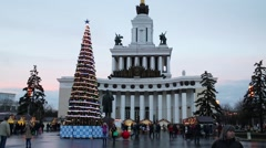 People walk near main pavilion and christmas tree in VDNH park Stock Footage