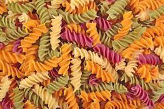 Colored uncooked italian pasta fusilli as background Stock Photos