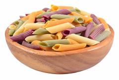 Colored uncooked italian pasta fusilli in a wooden bowl on a white - stock photo