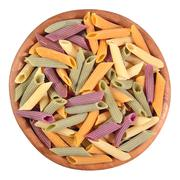 Colored uncooked italian pasta penne in a wooden bowl on a white - stock photo