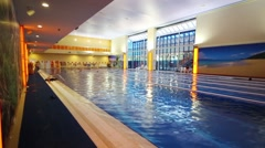 Modern empty indoor pool with pure water and resting people Stock Footage