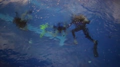 Ducking - diving instructor and two students under water in pool Stock Footage