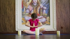 Girl sits on floor in pose of lotus near three candles Stock Footage