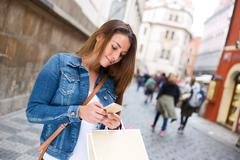 young woman reading her text messages in the street - stock photo