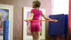 Girl in pink fast dances with red sport stick in gym hall Stock Footage