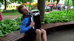 Charismatic man playing with accordion in the street, flycam move Stock Footage
