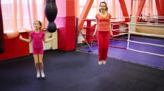 Girl and woman jump rope in gym hall with punching bags Stock Footage