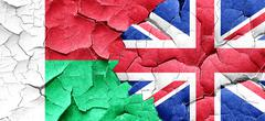 Madagascar flag with Great Britain flag on a grunge cracked wall - stock illustration