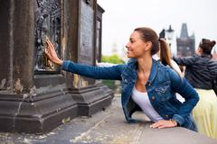 a young woman on Charles Bridge in Prague touching the shiny plaque and makin - stock photo