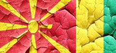 Macedonia flag with Guinea flag on a grunge cracked wall - stock illustration