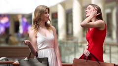 Two pretty girls with bags talk in big modern store Stock Footage