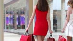 Back of two beautiful girls go with bags in shopping center Stock Footage