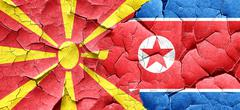 Macedonia flag with North Korea flag on a grunge cracked wall - stock illustration