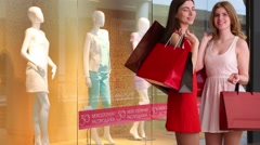 Two beautiful girls with bags stand near showcase with mannequins Stock Footage