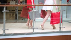 Legs of two girls with bags walking near railing in mall Stock Footage