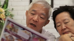 Asian senior couple looking at menus in a restaurant together Stock Footage