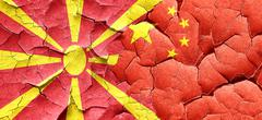 Macedonia flag with China flag on a grunge cracked wall - stock illustration