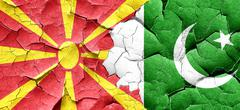 Macedonia flag with Pakistan flag on a grunge cracked wall - stock illustration