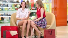 Two beautiful girls sit in shop and consider buying Stock Footage