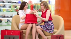 Two beautiful girls sit in shopping center and talk Stock Footage