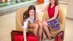 Two girls sit in leather armchairs with purchases in mall Stock Footage