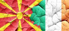 Macedonia flag with Ireland flag on a grunge cracked wall - stock illustration