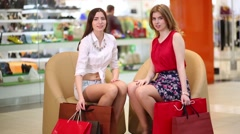 Two beautiful girls sit in armchairs with bags and go away in mall Stock Footage