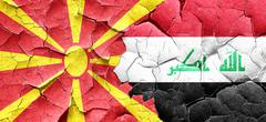 Macedonia flag with Iraq flag on a grunge cracked wall - stock illustration