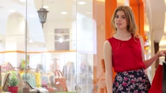 Beautiful girl in skirt stands with bags near showcase in mall Stock Footage