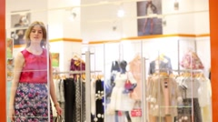 Beautiful girl in skirt with bags exits of shop in mall Stock Footage