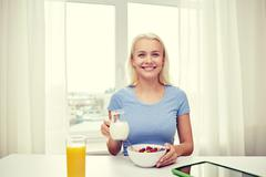 woman with milk and cornflakes eating breakfast - stock photo