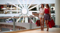 Two beautiful girls walk with purchases in big mall Stock Footage