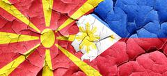 Macedonia flag with Philippines flag on a grunge cracked wall - stock illustration